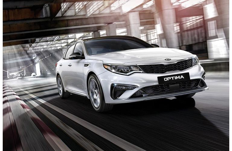 2020 Kia Optima exterior shot with silver paint color driving through an empty warehouse hangar as light shines through glass windows