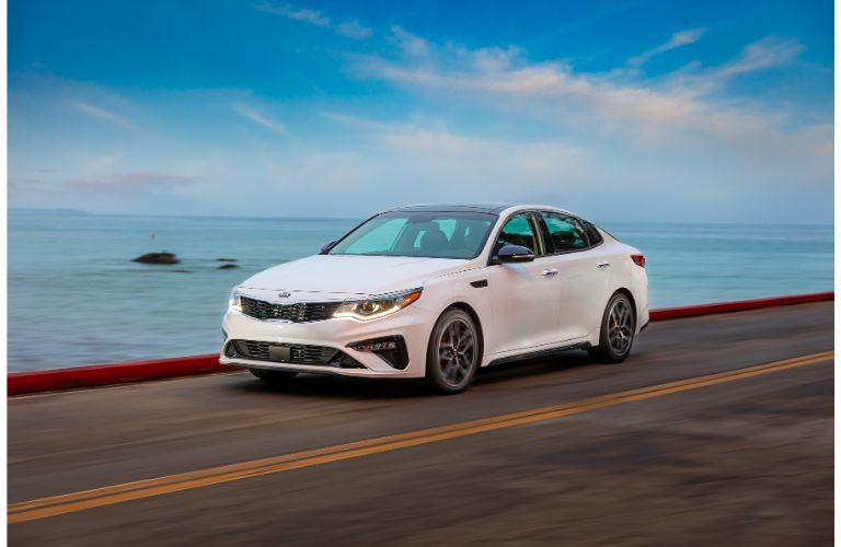 2020 Kia Optima exterior shot with white paint color driving down a highway near the sea and a blue sky