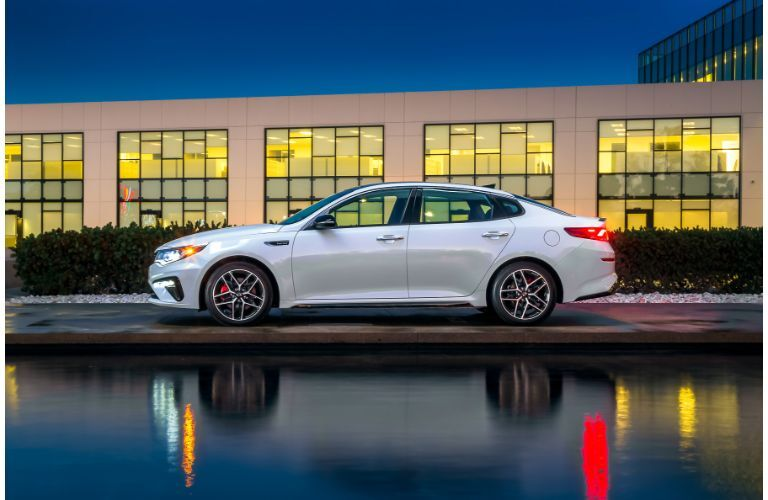 2020 Kia Optima exterior side shot with white paint color parked outside a car dealership near a pond at night