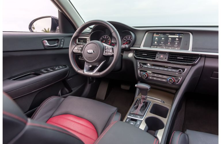 2020 Kia Optima interior shot of front seating upholstery, steering wheel, transmission, and dashboard layout