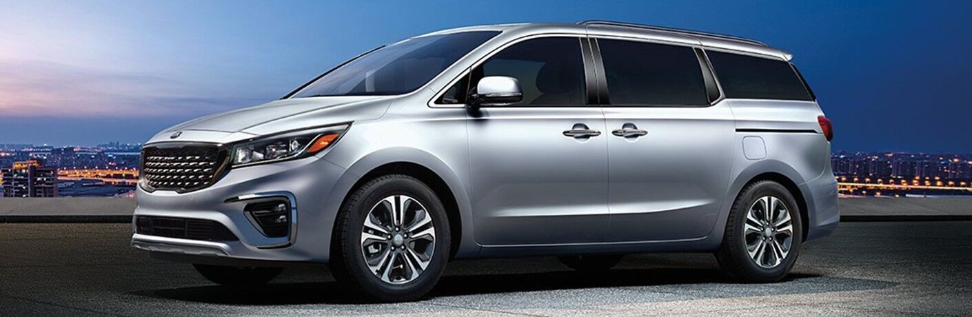 2020 Kia Sedona exterior side shot with silver paint color parked on a building rooftop with a night city skyline in the background