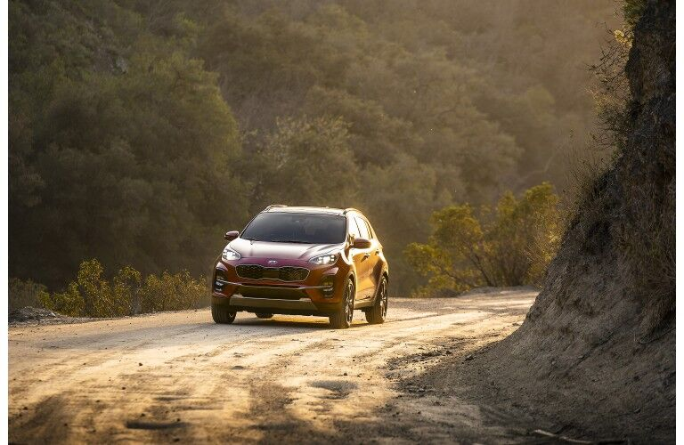 2020 Kia Sportage SUV redesign exterior far away shot with red paint color as it drives through a dirt gravel road in the wilderness under a setting sun