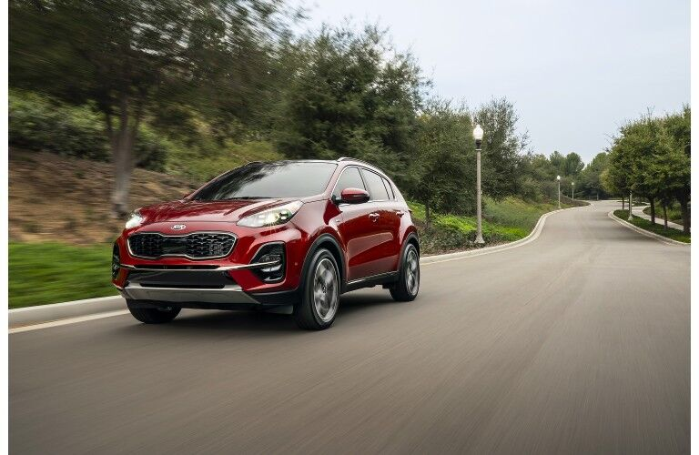 2020 Kia Sportage SUV redesign exterior shot with red paint color driving down an empty suburban forest road framed by streetlight lamps
