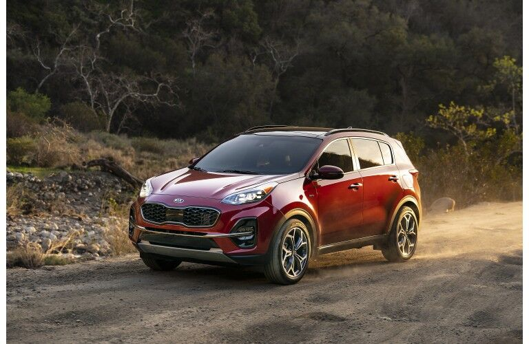 2020 Kia Sportage SUV redesign with red paint color parked on a dirt forest road