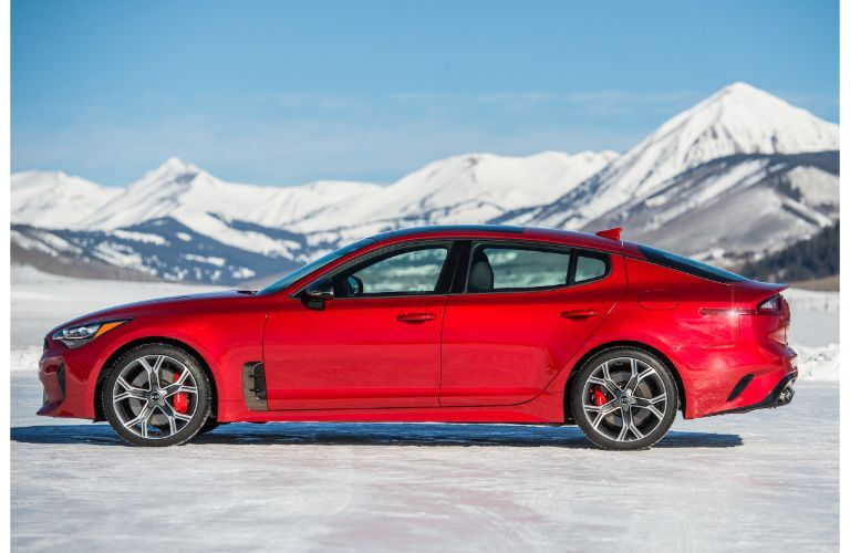 2020 Kia Stinger GT2 exterior side shot with red paint color parked on a snowy and icy tundra