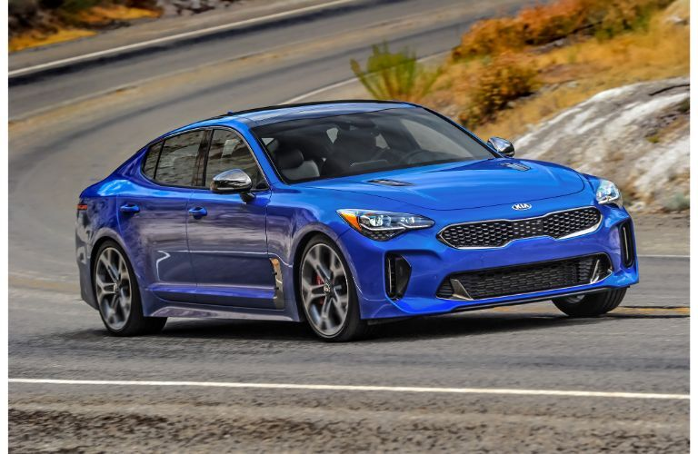 2020 Kia Stinger GT2 with AWD exterior shot with blue paint color driving around a desert highway corner