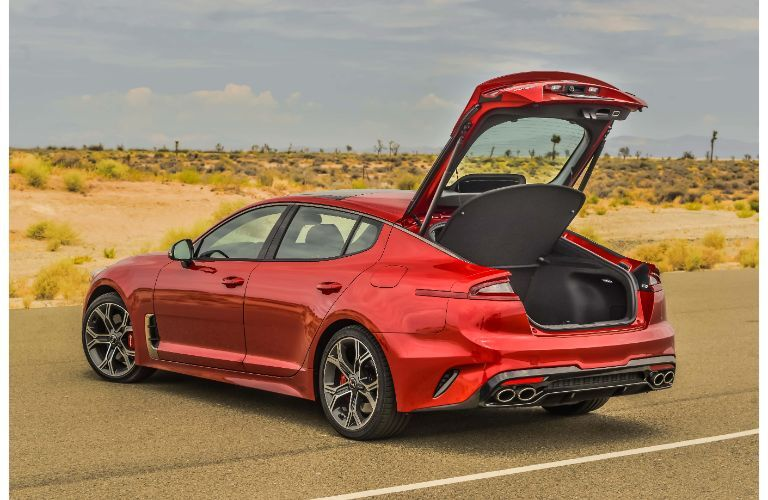 2020 Kia Stinger GT2 with AWD exterior shot with red paint color parked on a desert highway with its trunk popped open