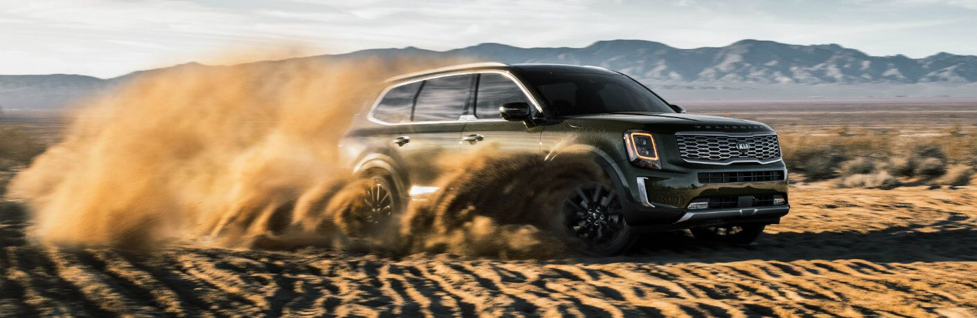 2020 Kia Telluride SUV exterior shot with moss green paint color driving through a desert as it kicks up clouds of sand