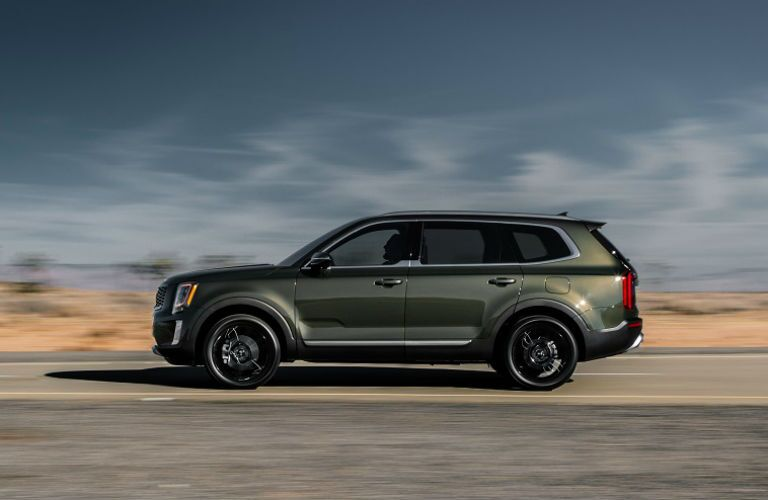 2020 Kia Telluride exterior side shot with dark moss green paint color parked in the middle of a desert road