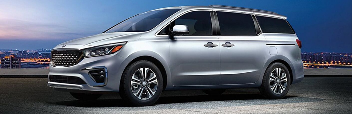 2021 Kia Sedona minivan exterior shot with Silky Silver paint color parked on a roof overlooking a dark blue sky and city lights
