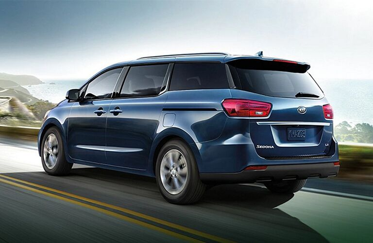2021 Kia Sedona minivan exterior side rear shot with blue paint color driving on a country mountain highway