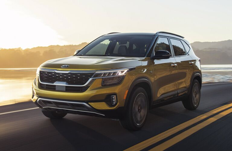 2021 Kia Seltos exterior shot with Starbright Yellow paint color driving alongside a coastal highway near the ocean