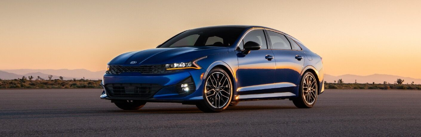 2021 Kia K5 exterior shot with Sapphire Blue Paint color parked on an empty lot at sunset