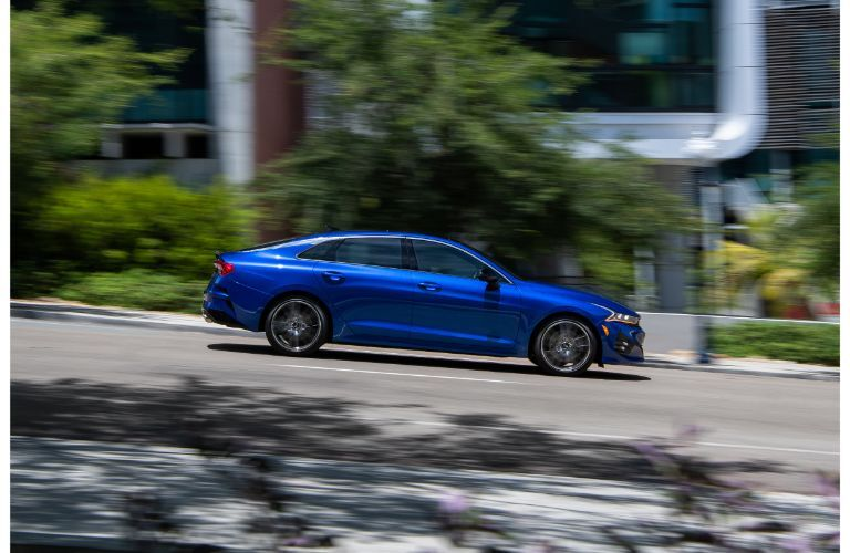 2021 Kia K5 exterior side shot with Sapphire Blue paint color driving down a suburban street hill