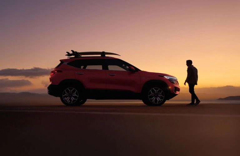 2021 Kia Seltos exterior side shot with red paint color parked in a sand dune at sunset
