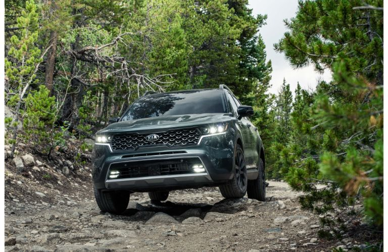 2021 Kia Sorento exterior front shot of grille and headlights driving on a forest trail