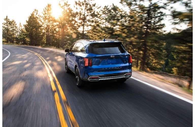 2021 Kia Sorento exterior rear shot with blue paint color driving on a country highway