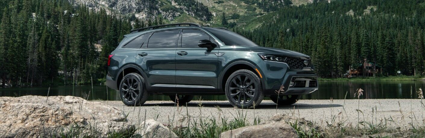 2021 Kia Sorento exterior side shot parked on a gravel field with a background of forest trees and mountains