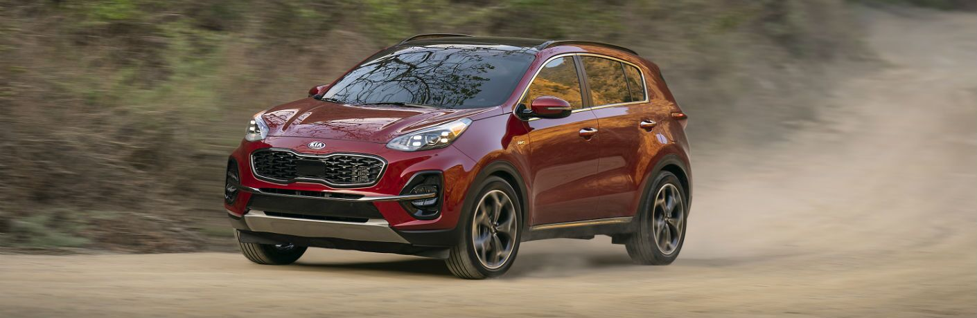 A front left quarter photo of the 2021 Kia Sportage in motion on a dirt road.