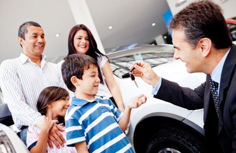 a salesman handing off the keys for a new car purchase at a dealership to the son of a family