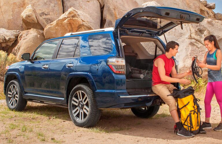 Rear Driver View of a blue 2019 Toyota 4Runner with the Back Open and Two People Handing Off Supplies