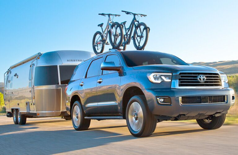 Blue 2019 Toyota Sequoia Driving with Two Bikes Mounted on Top and Pulling a Silver Trailer Behind