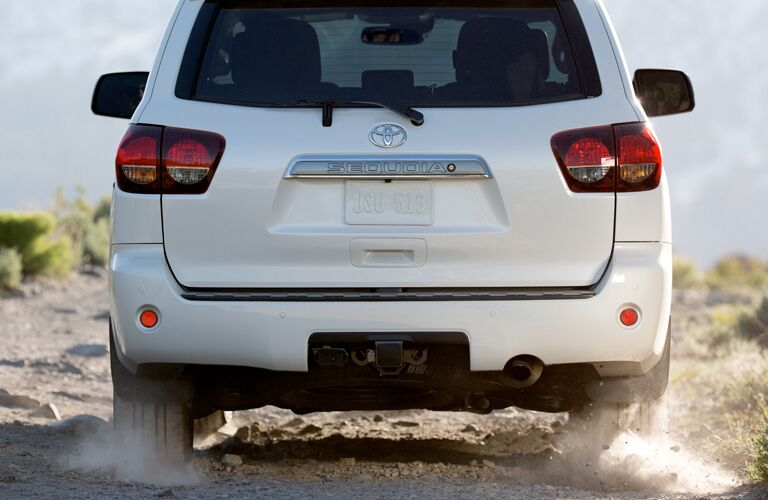 Rear Side of a White 2019 Toyota Sequoia Driving down a dirt road