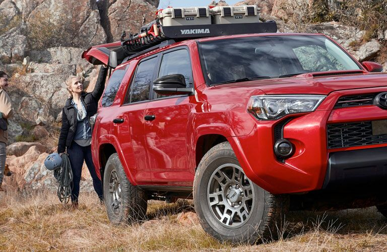 Red 2020 Toyota 4Runner from front passenger side angle with woman getting stuff from trunk