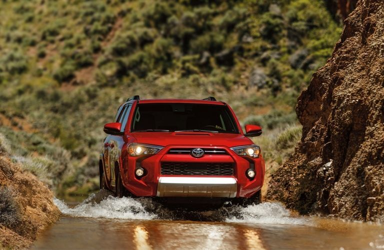2020 Toyota 4Runner TRD Off-Road Premium driving through a stream with cliffs on either side