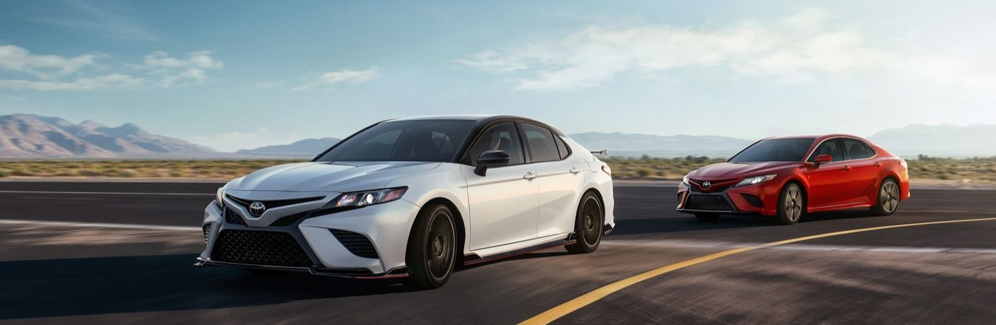 2020 Toyota Camry TRD driving in front of Camry XSE V6