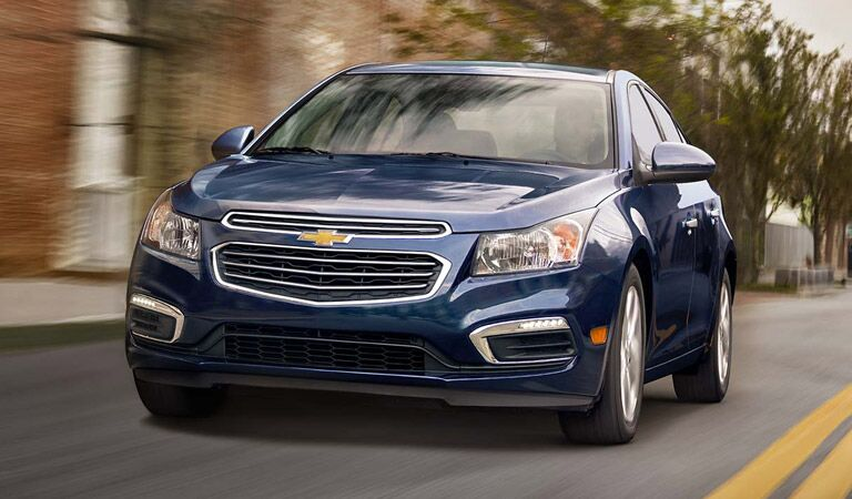 Blue Chevy Cruze driving past houses
