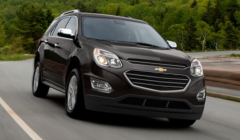 Black Chevy Equinox driving near the forest