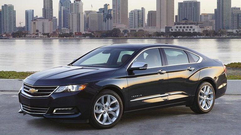 black 2015 Chevy Impala in front of a lake and a city