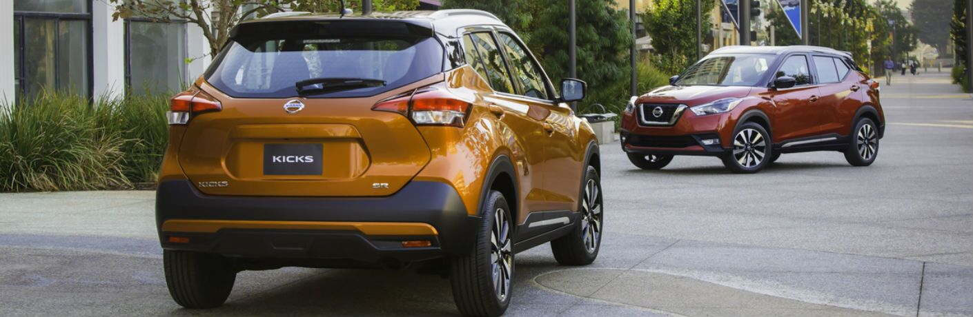 A photo of two models of the 2018 Nissan Kicks parked on a street.