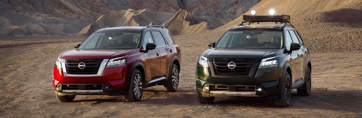 A photo of two 2022 Nissan Pathfinder models parked in the desert.