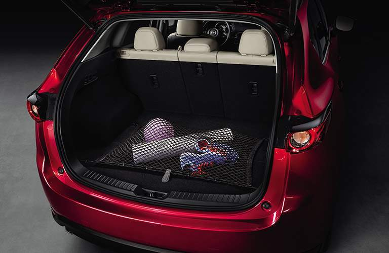 Rear tailgate of the 2018 Mazda CX-5 open and loaded with cargo under the available cargo net