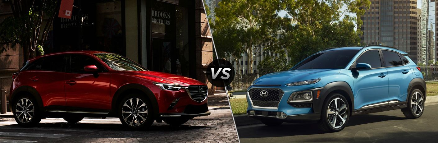 "Passenger side exterior view of a red 2019 Mazda CX-3 on the left ""vs"" driver side exterior view of a blue 2019 Hyundai Kona on the right"
