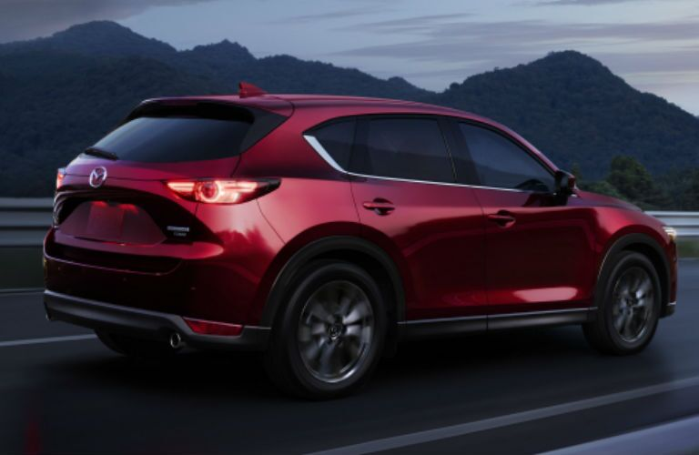 An external side view of a red-colored 2021 Mazda CX-5 as it drives on a roadway