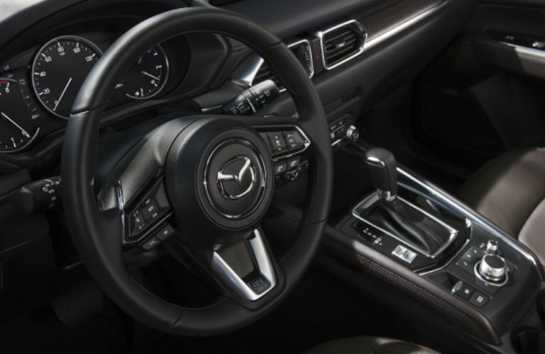 A close view of the steering wheel and other controls in the driver area of the 2021 Mazda CX-5