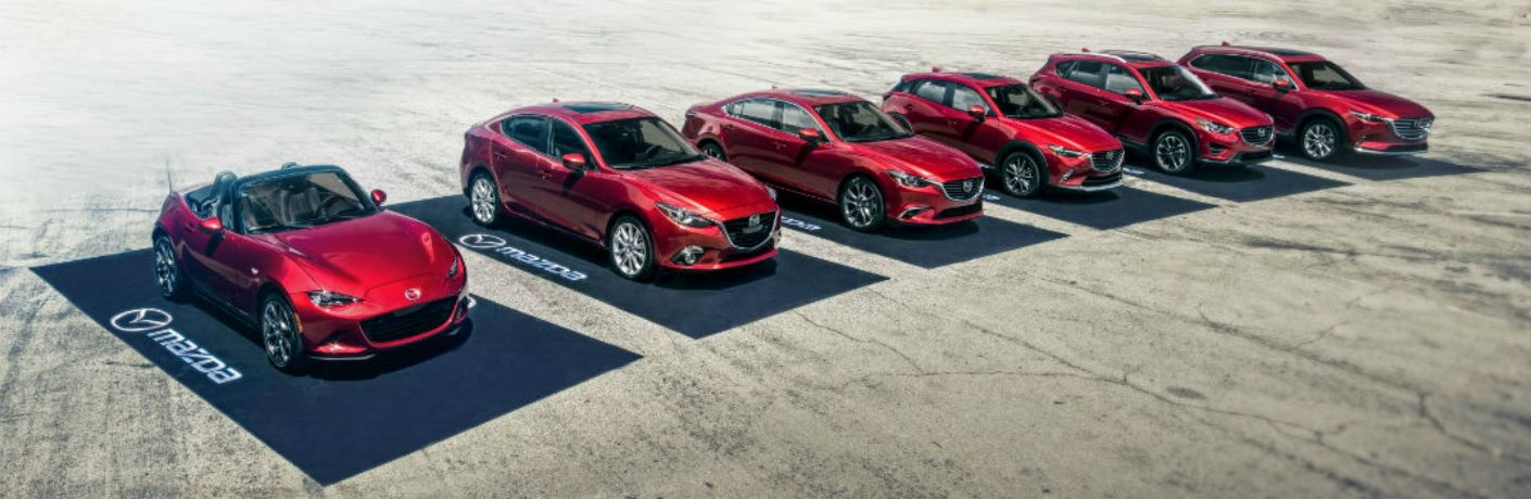 2018 Mazda vehicle lineup parked next each other on black mats in the desert