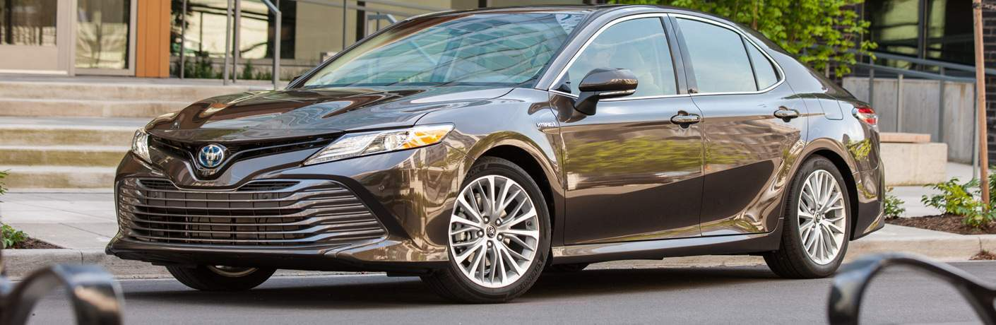 Quarter front profile of the 2018 Toyota Camry Hybrid parked by front steps