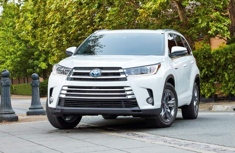 2018 Toyota Highlander Hybrid parked on a concrete road by a grove of trees