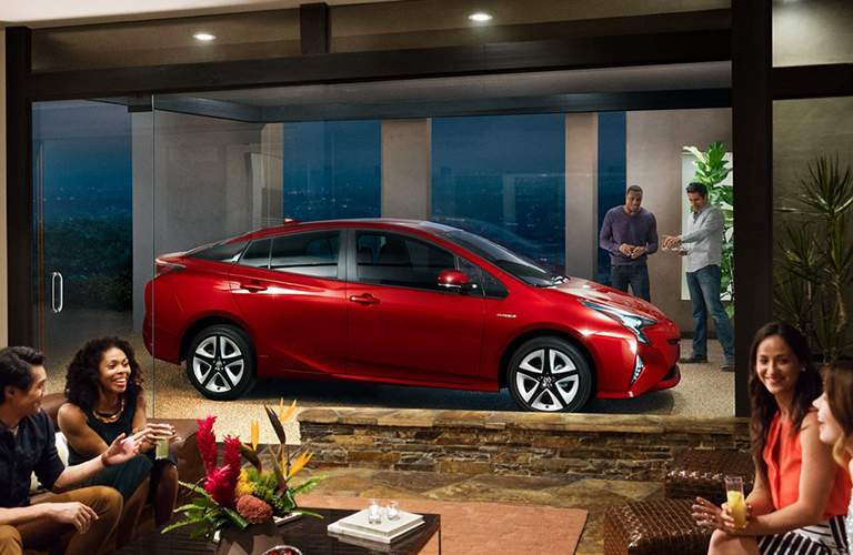 Two people looking at the 2018 Toyota Prius parked outside a glass door with four people socializing inside