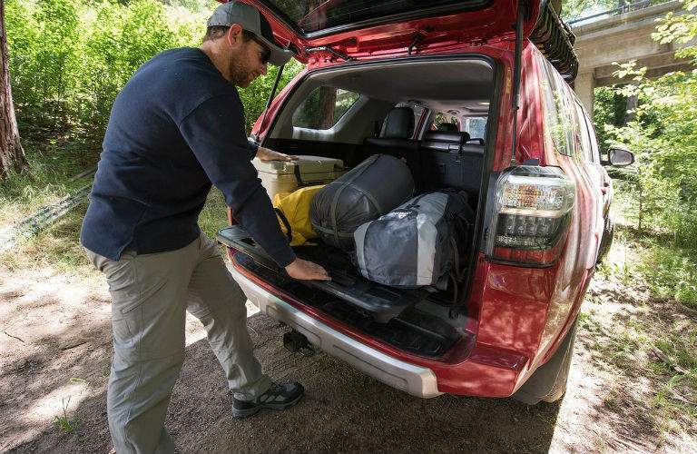 Man using the available sliding cargo deck to remove items from the trunk of the 2018 Toyota 4Runner