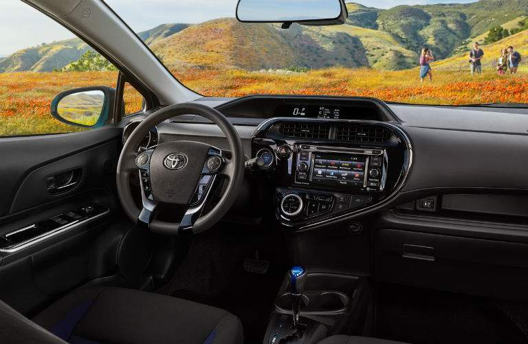 Front seat of the 2018 Toyota Prius c with focus on steering wheel and infotainment system
