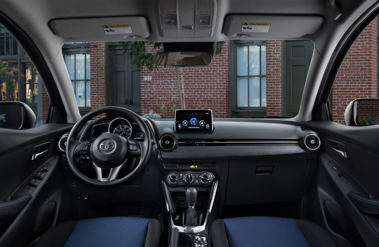 Front cockpit of the 2018 Toyota Yaris iA with focus on the steering wheel and display screen looking at a brick building
