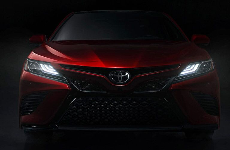 Front view of a red 2019 Toyota Camry in a dark envrionment