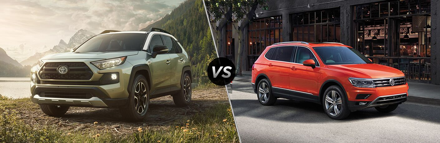 Front driver angle of a green 2019 Toyota RAV4 on left VS front passenger angle of an orange 2019 Volkswagen Tiguan on right