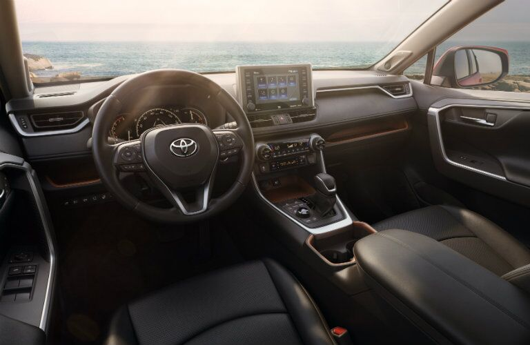 Close up of the steering wheel and front interior with the ocean in the background through the windshield