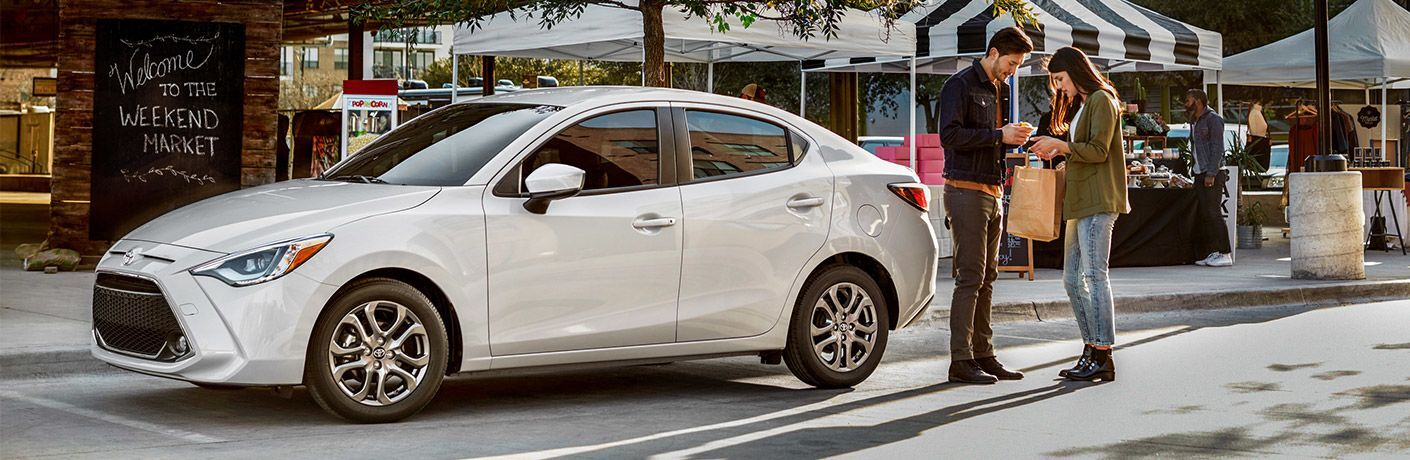 2019 Toyota Yaris exterior front fascia and drivers side parked with couple standing behind at marketplace